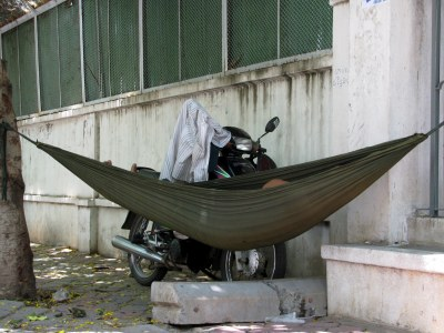 <em>This</em> sleeping motodup driver prefers the comfort of his own hammock to the comfort of his motorbike seat. And who could blame him? (re the shirt: It's fucking hot here!)